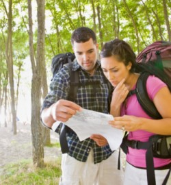 Couple in backpacks looking at map