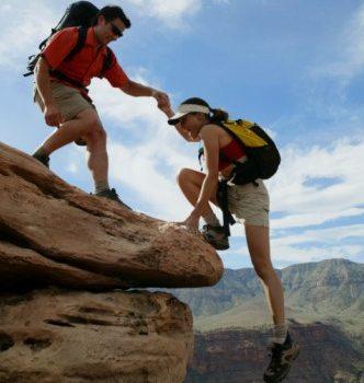 Couple climbing rocks